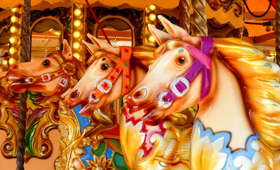 Close up of three hand painted carousel horses or gallopers on a fairground ride in an amusement park