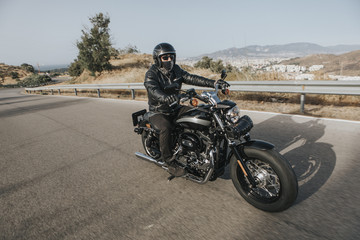 Man in black clothes riding a black classic American motorcycle in a road.