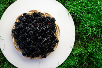Blackberry in basket  on a white table grass background, top view.