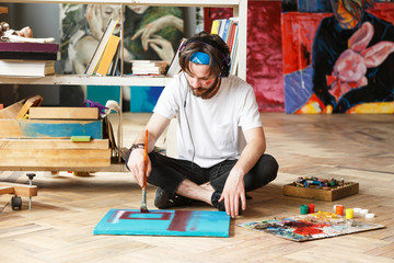 Creative dark-haired bearded hipster male artist in headphones and blue bandana sitting on the floor and and drawing with oil and brush on canvas in his contemporary studio with many paintings.