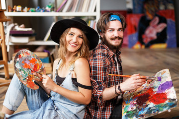 Two pretty smiling artists dressed in hipster clothes holding brushes and mixed colors on the palette in contemporary studio with many paintings