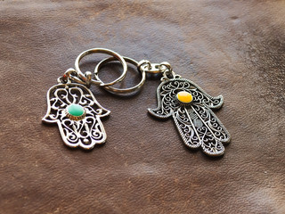 Two key rings in the form of Fatima Hand on a brown leather background. Ancient symbol and traditional modern tourist souvenir of Tunisia