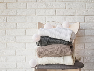 Wall Mural - Stack of knitted sweaterson the brick wall background