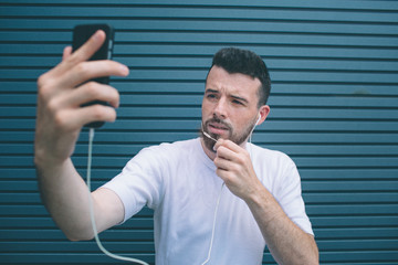 Guy is posing on camera. He is taking selfie and holding one hand on chin. Also man is listening to music. Isolated on striped and blue background.