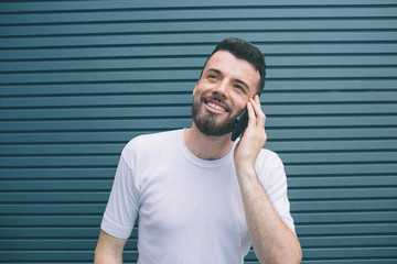 Happy guy is holding and talking on the phone. He is looking up. Isolated on striped and blue background,