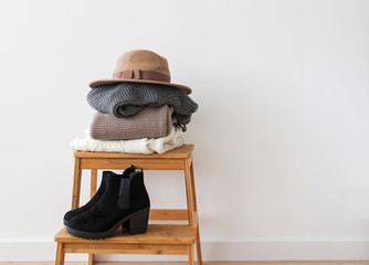 Wall Mural - Stack of knitted sweaters, hat and boots near the white wall.