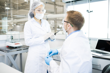 Portrait of two modern young scientists wearing lab coats discussing project while working in medical laboratory