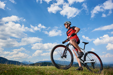 Profile of young athletic tourist biker in professional sportswear starting to cycle a bike on distant mountains and blue summer sky background. Active lifestyle and extreme sport concept.