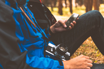 Traveler man backpacker using a smart phone in forest
