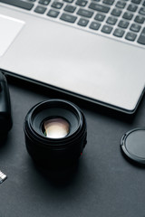 Work space on black table of photographer. Minimal workspace with Laptop, camera and lens copy space on dark background. Modern and elegant. Close up.
