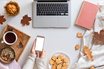 View from above of autumn background with mobile phone, laptop, autumn leaves, cookies, vintage book on white workspace. Top view and flat lay