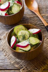 Healthy salad with radishes and cucumbers in a wooden bowl.
