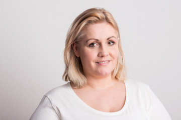 Portrait of an attractive overweight woman in studio on a white background.