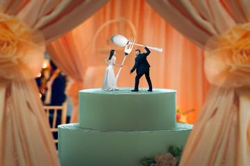 Wedding cake, figurines hold huge cutlery in hands