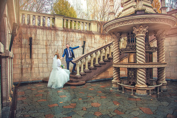 Groom holds bride's hand and shows way to top, on stone staircase, in open air, in fall