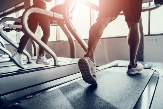 Close up. Man and Young Woman on Treadmills in Gym