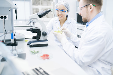 Portrait of two modern young scientists smiling while doing research studying food substances in laboratory, copy space