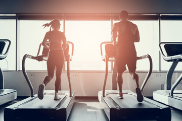 Bearded Man and Young Woman on Treadmills in Gym.