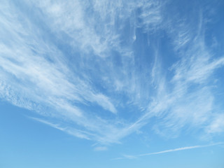 Blue sky with white feathery clouds in sunny day. Cirrus clouds as beautiful weather background