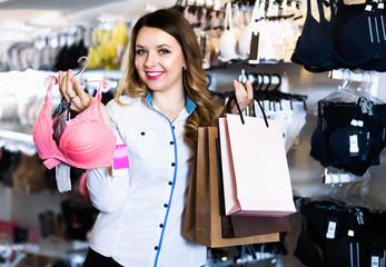 Female shopper boasting her purchases in underwear shop