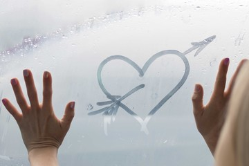 Heart on the fogged glass. A female hand drew a heart.