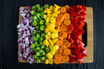 Chopped fresh vegetables  on the cutting board on the black wooden background.Top view.