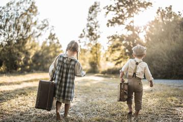 Kinder mit Koffer laufen über die Wiese