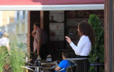 Kobieta, biznesmen pali papierosa przed restauracją.