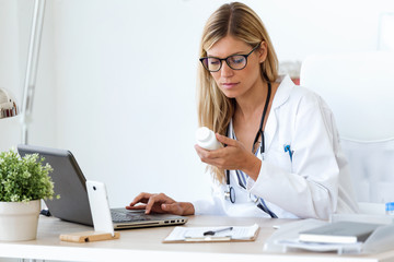 Female doctor working with laptop and researching some medication information in the consultation.