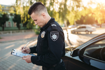 Male police officers writes a fine on the road