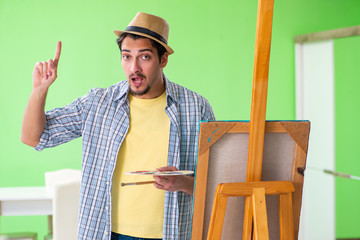 Young male artist working on new painting in his studio