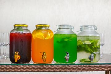 four glass jars with different lemonade mojito, tarragon, cherry, orange