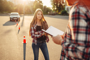 Fototapete - Male instructor and female student, driving school