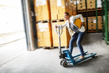 Customs female  manager drives forklift in the warehouse.Positive and fun business concept.