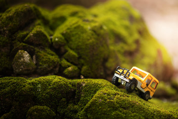 Four by four off road car crossing through  the mountain covered with green moss. Travel and racing concept for four wheel drive off road vehicle .