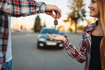Fototapete - Driving teacher gives the keys to female student