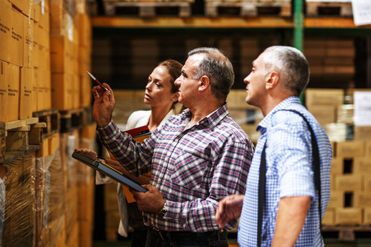 Team of customs managers and warehouse worker checking list and inventory on the shelf in storehouse.