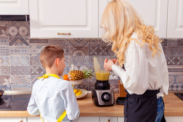 A woman prepares a drink in a blender, the son helps.