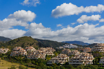 Modern hauses and green golf field on mountains against cloudy sky in Spain.Costa del sol. Andalusiya.