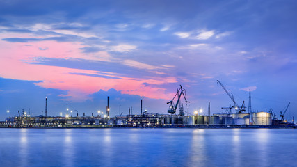 Panorama of a petrochemical production plant against a dramatic colored cloudy sky at twilight, Port of Antwerp, Belgium.