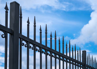 Beautiful decorative cast metal wrought fence against blue sky. Iron guardrail close up.