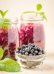 Raw blueberry smoothie with ripe wild forest berries and green mint leaves.