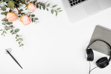 Styled white office desktop with keyboard, earphones, pink roses, eucaliptus branches, notebook and calligraphy pen. Top view of workspace mockup, flat lay, copy space