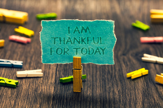 Conceptual hand writing showing I Am Thankful For Today. Business photo showcasing Grateful about living one more day Philosophy Paperclip retain blue cardboard blurry woody desk paper clip.