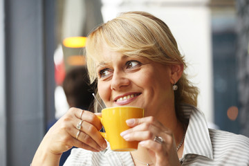 Smile blond woman with yellow cup with coffee