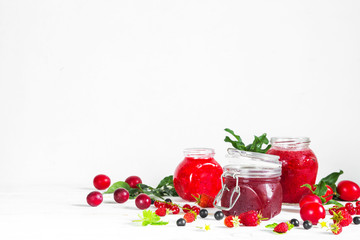 assortment of jams, seasonal fresh berries and fruits on white background