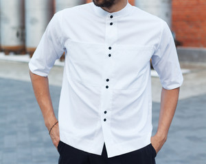 Youth street fashion for men. A man in a summer day in the street in a fashionable outfit. White trendy shirt and black trousers. Part of the body.