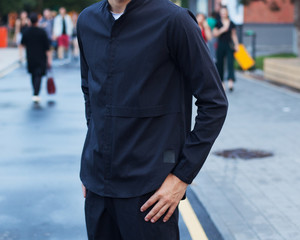 Youth street fashion. A man in the afternoon on a summer street in a fashionable outfit. Black trousers and shirt. Part of the body.