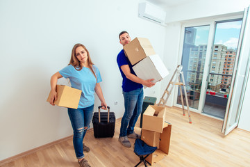 Portrait of married couple with luggage and boxes moving into a new apartment. Young family moving in a new apartment concept.