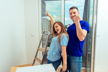 Happy smiling couple in their new flat. Young family moving in a new apartment concept.